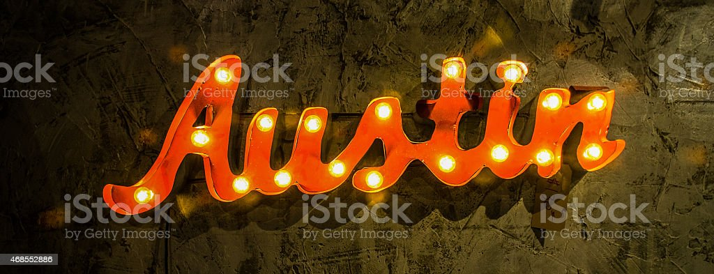 wide shot austin light up wall sign on textured wall stock photo