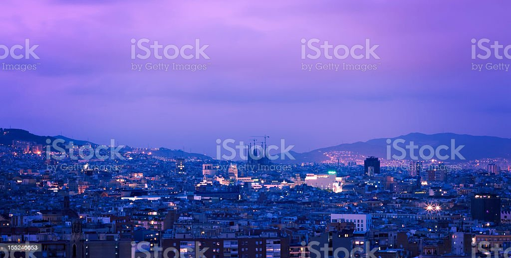 Wide shot of Barcelona at night under a purple sky royalty-free stock photo