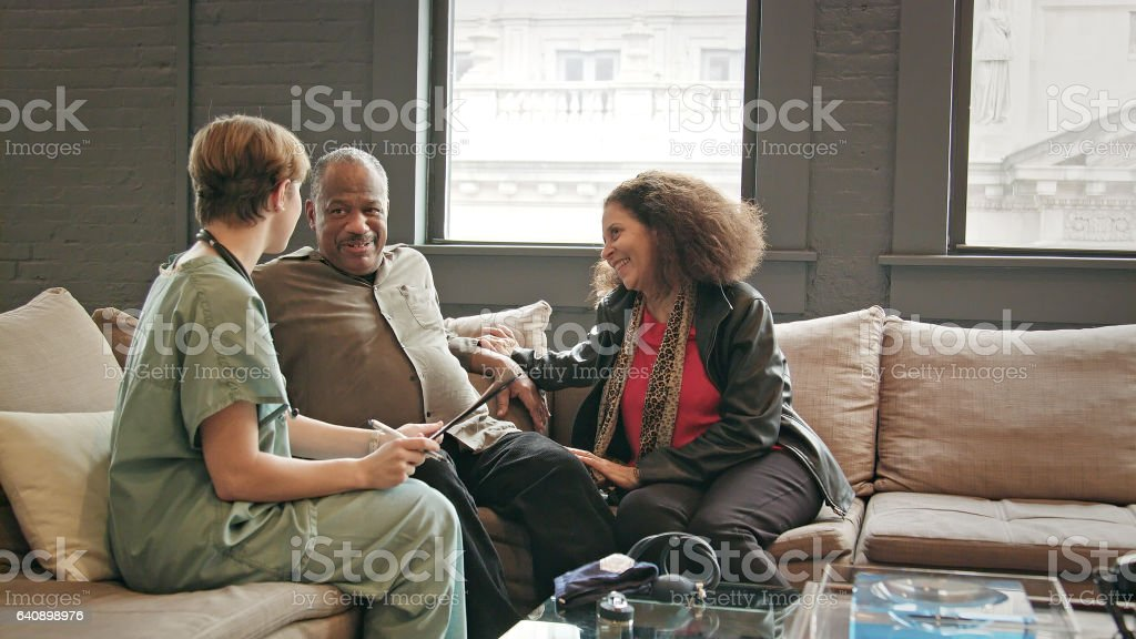 Wide Shot of Home Healthcare Provider Visiting with Senior Couple stock photo