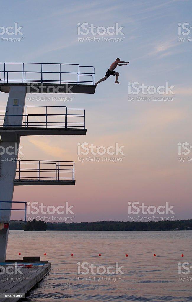 Wide shot of man jumping into lake at sunset royalty-free stock photo