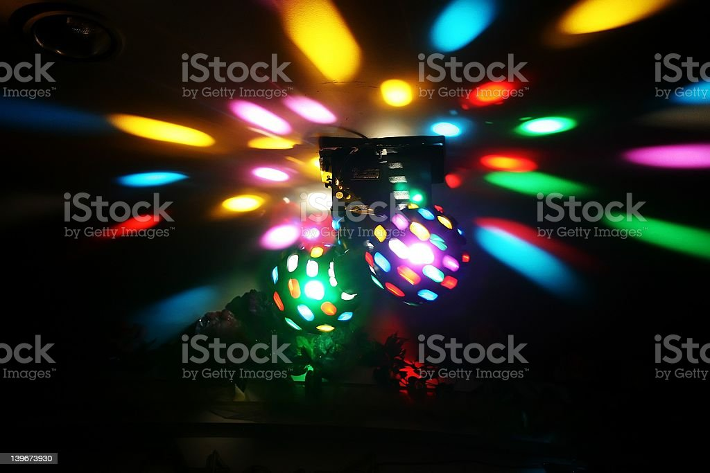 Wide shot of two multicolored disco lights in a dark room stock photo
