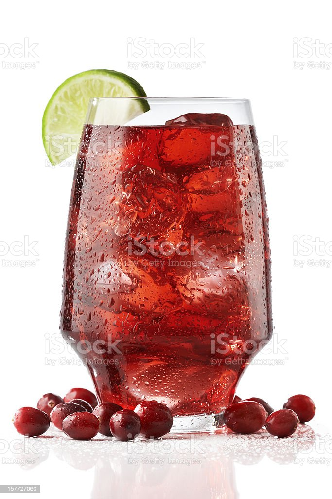 A wide tall glass of fresh cranberry juices served with lime stock photo
