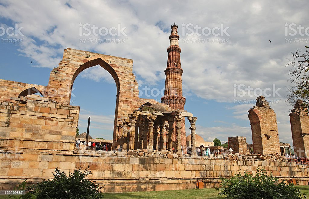 Wide view of the Qutub Minar Ruins packed with tourists stock photo