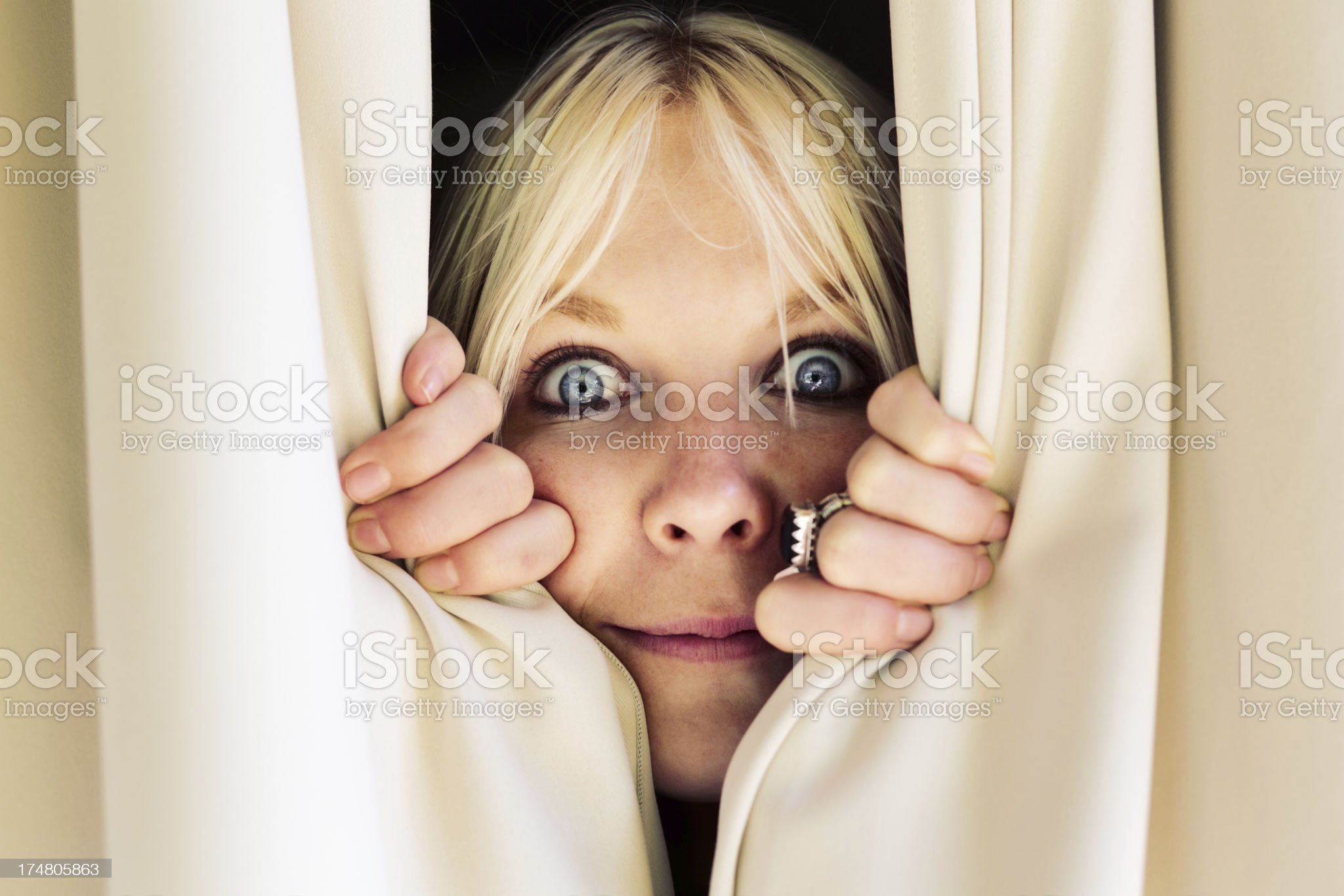 Wide-eyed blonde woman looks though closed curtains royalty-free stock photo