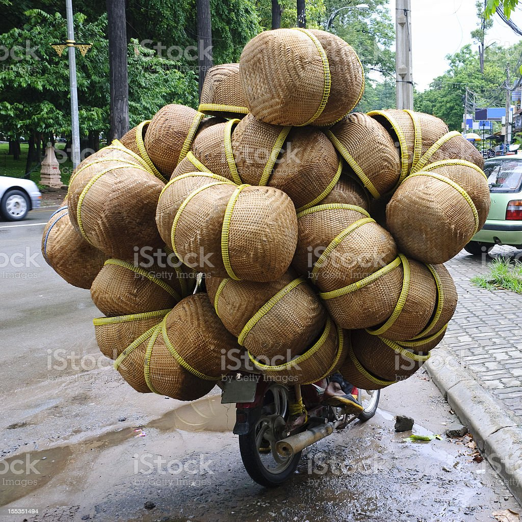 Wide-load of woven baskets on motorcycle in Cambodia stock photo