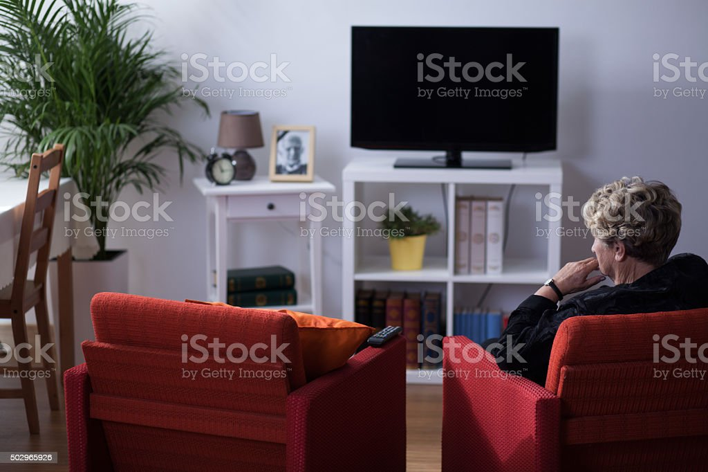 Widow sitting in living room stock photo