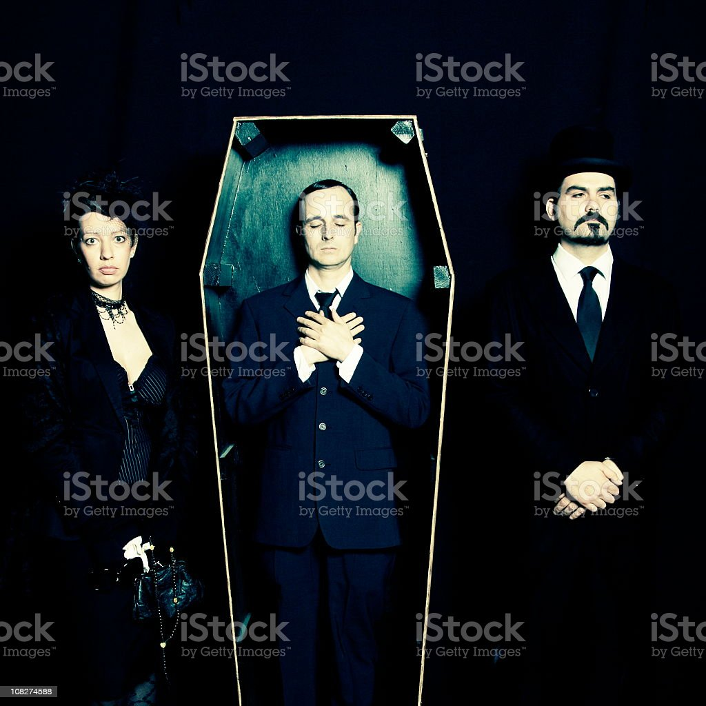 Widow, undertaker and man in coffin royalty-free stock photo