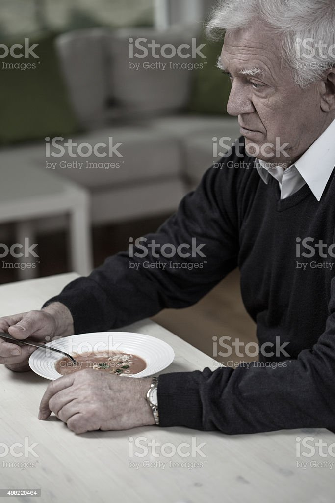 Widower eating meal stock photo