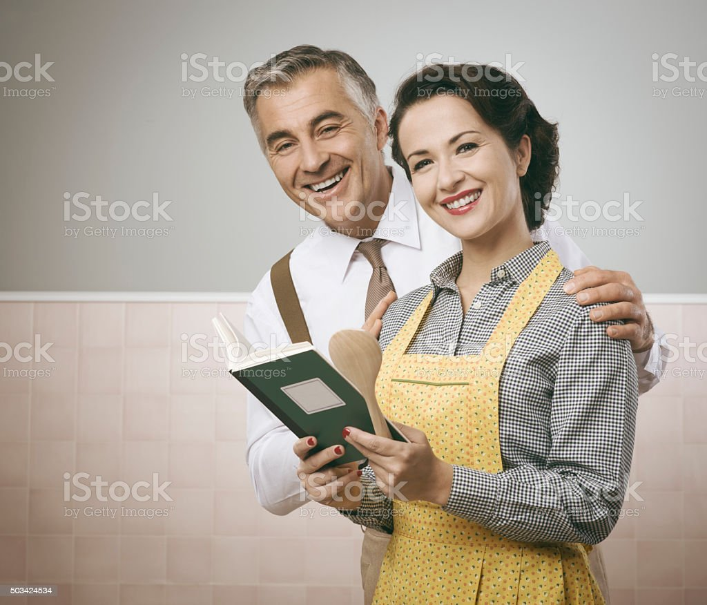 Wife and husband reading a cookbook together stock photo
