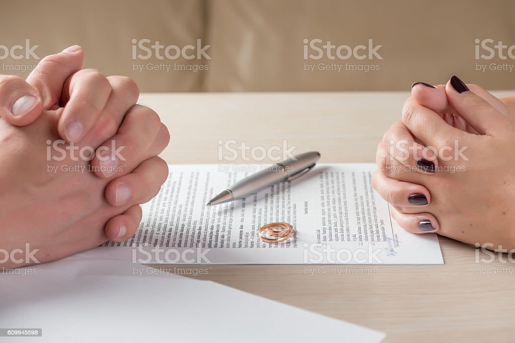 wife and husband signing divorce documents or premarital agreement stock photo