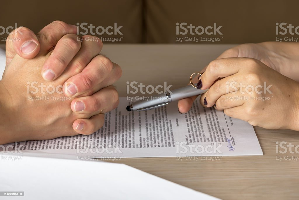 Wife and husband signing divorce documents, woman returning wedding ring stock photo