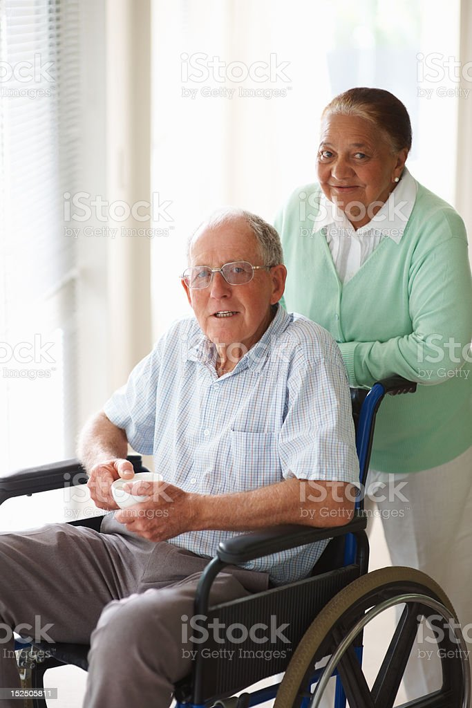 Wife assisting husband sitting on wheelchair royalty-free stock photo