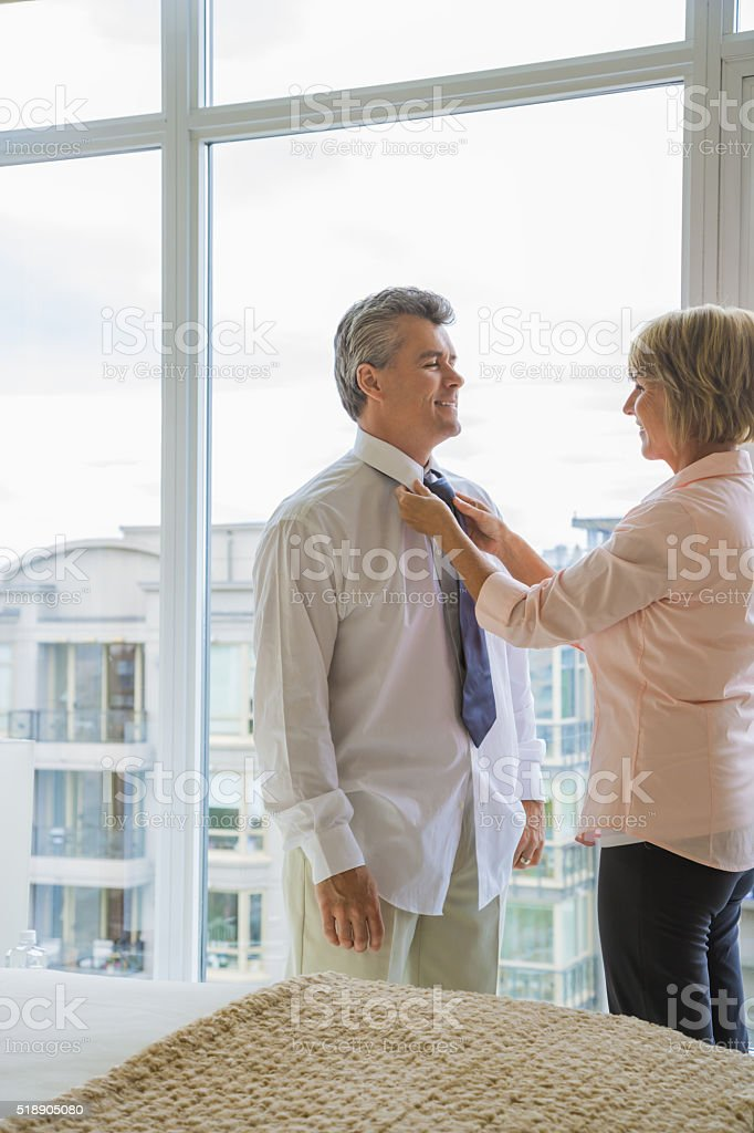Wife assisting husband with necktie stock photo