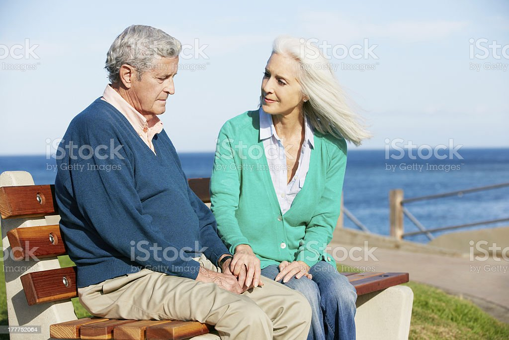 Wife comforting her depressed husband on a seaside bench royalty-free stock photo