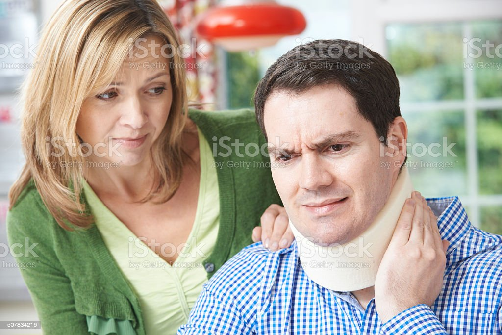 Wife Comforting Husband Suffering With Neck Injury stock photo