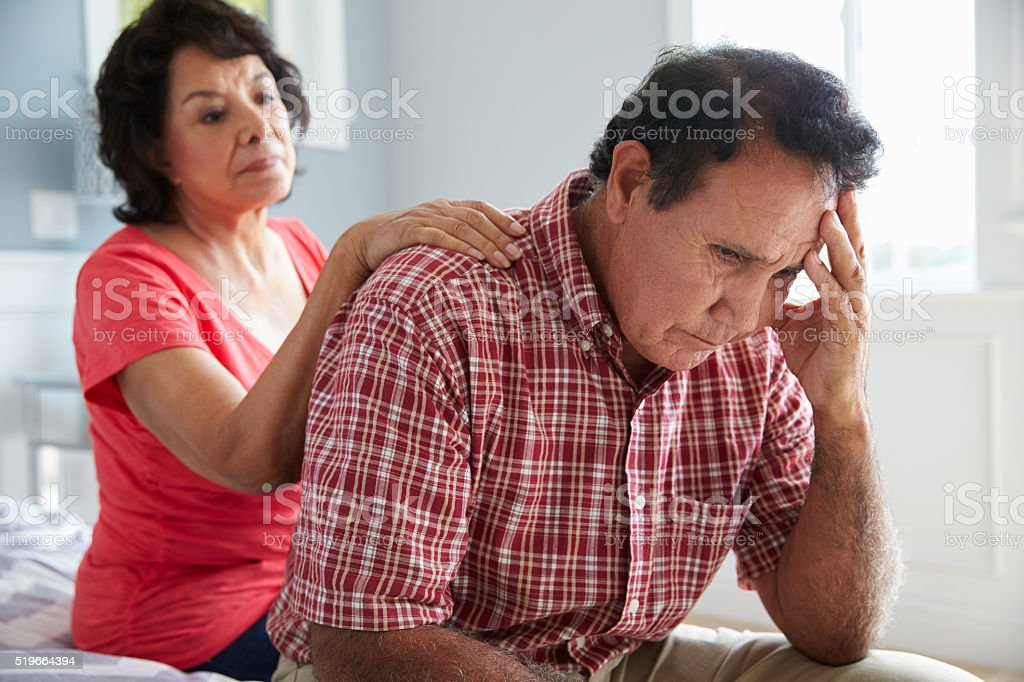 Wife Comforting Senior Husband Suffering With Dementia stock photo