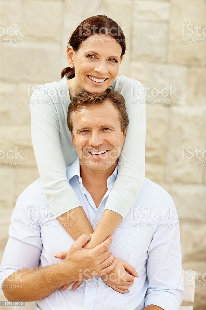 Wife embracing her husband from behind royalty-free stock photo