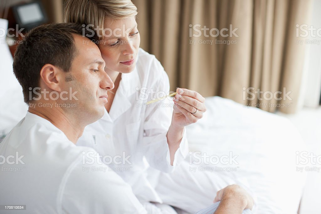 Wife taking husband's temperature royalty-free stock photo