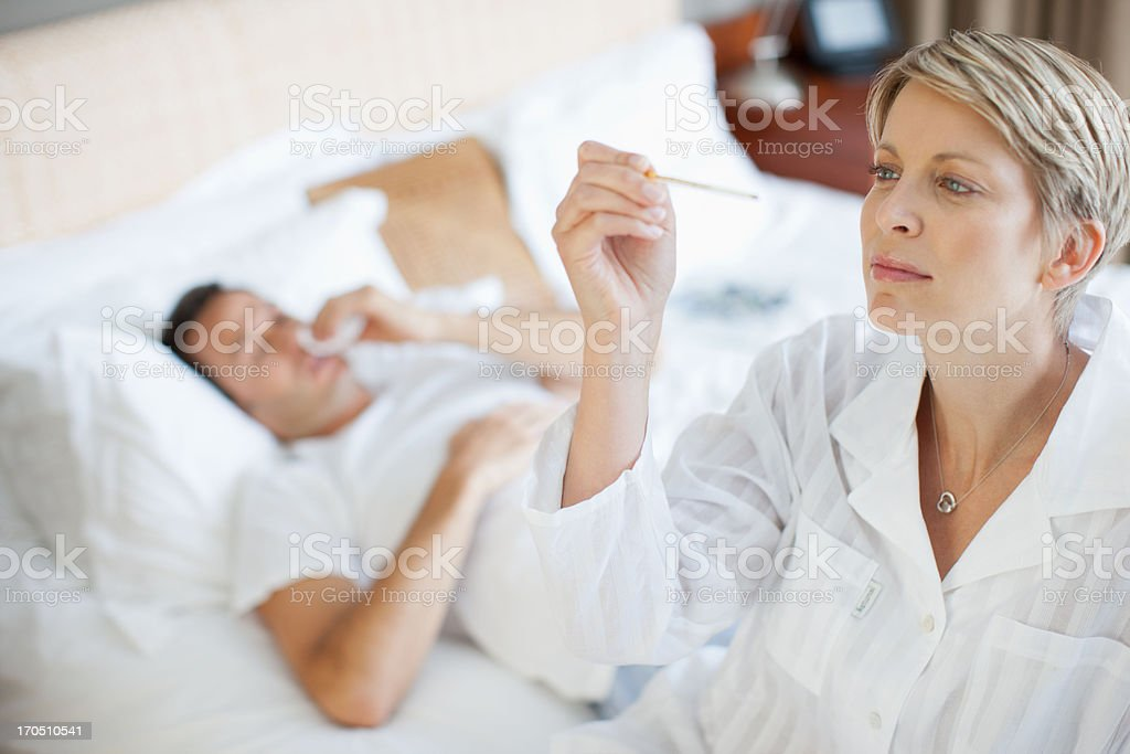 Wife taking wife's temperature royalty-free stock photo
