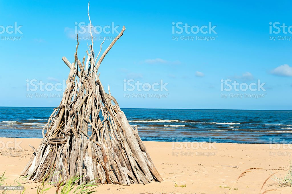 Wigwam Made from wooden branches on the baltic sea beach stock photo