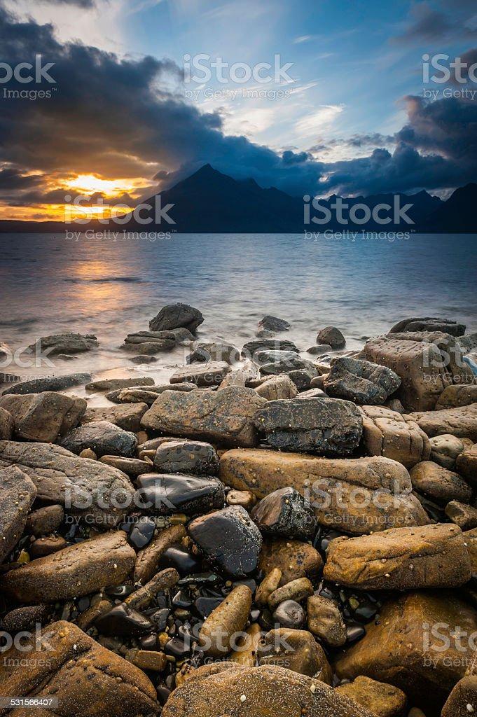 Wild beach ocean sunset over Cuillin mountains Highlands Skye Scotland stock photo
