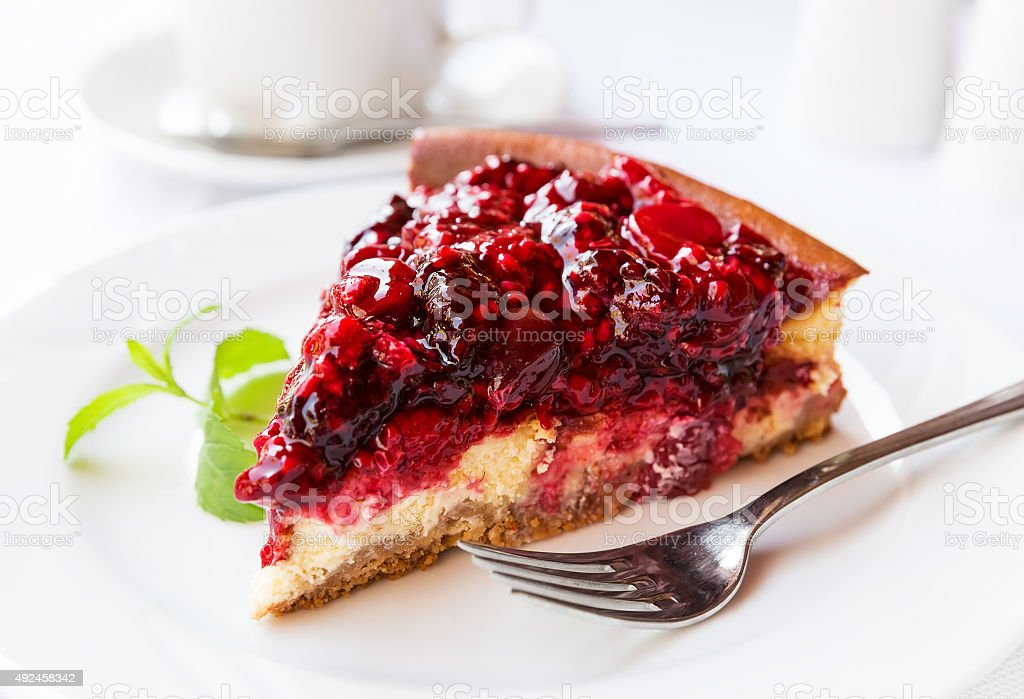 Wild berries cake with green mint on plate with fork stock photo