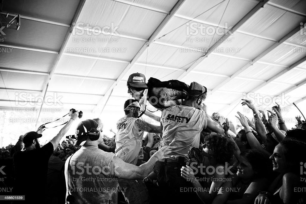 Wild fan crowd surfing stock photo