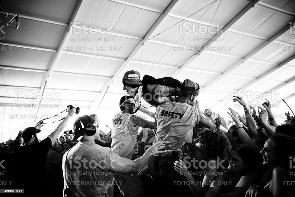 Wild fan crowd surfing stock photo