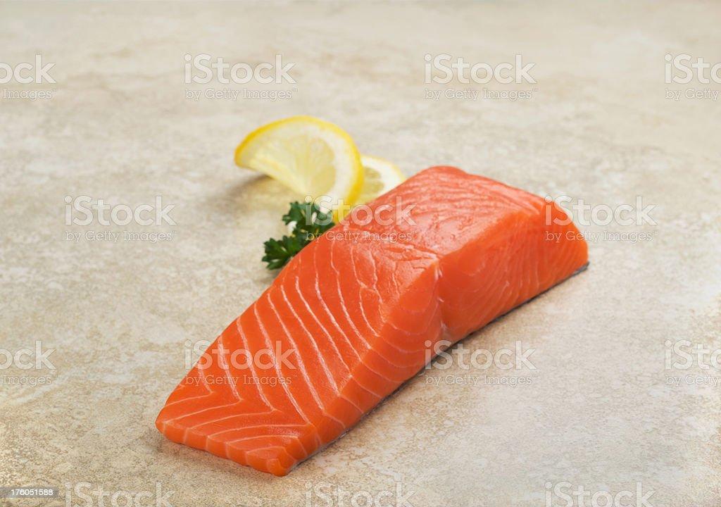 Wild King Salmon Slice, Raw, on Stone with Lemon royalty-free stock photo