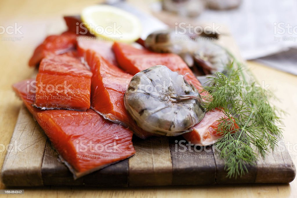 Wild Salmon raw fillet and prawns on cutting board royalty-free stock photo