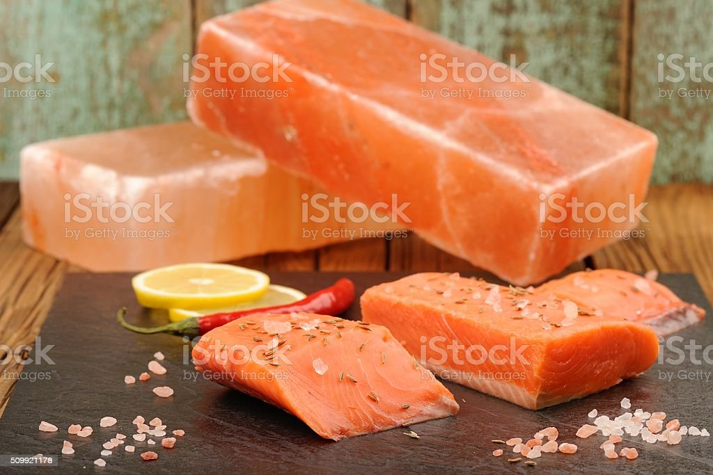 Wild salmon salted with himalayan pink salt blocks, lemon stock photo