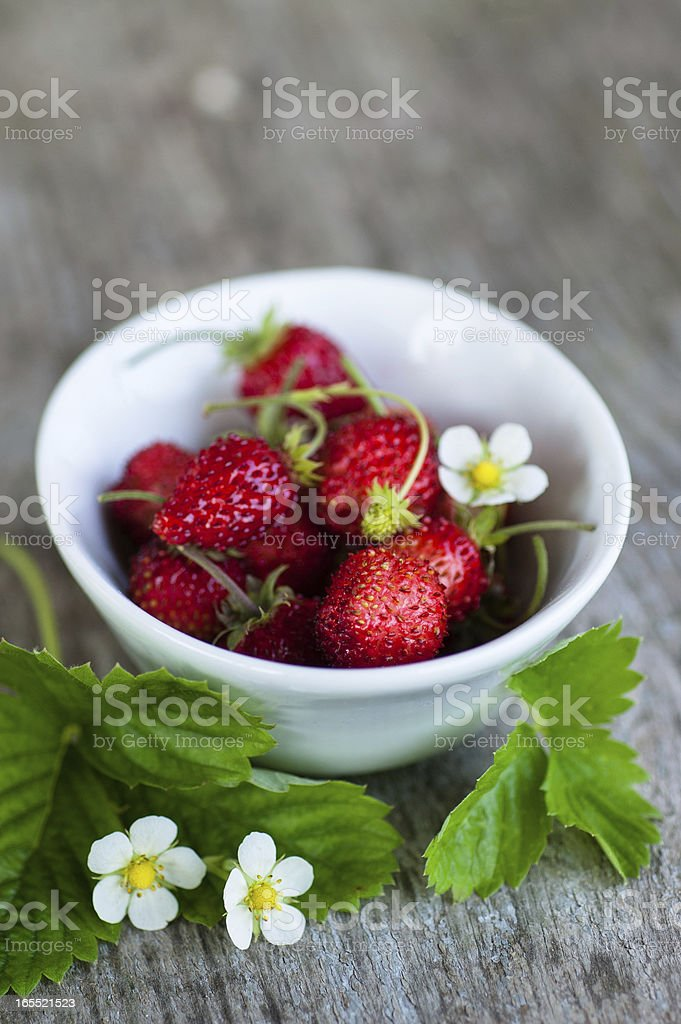 Wild strawberries in white bowl on wooden background royalty-free stock photo