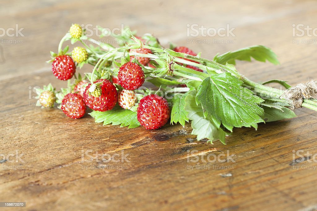 Wild strawberries on wooden background royalty-free stock photo