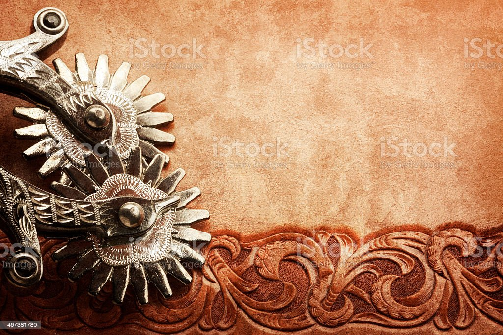 Wild west spurs on a tooled leather surface stock photo