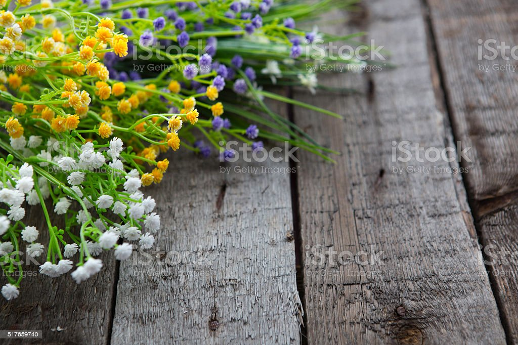Wildflowers on the background of wood. stock photo