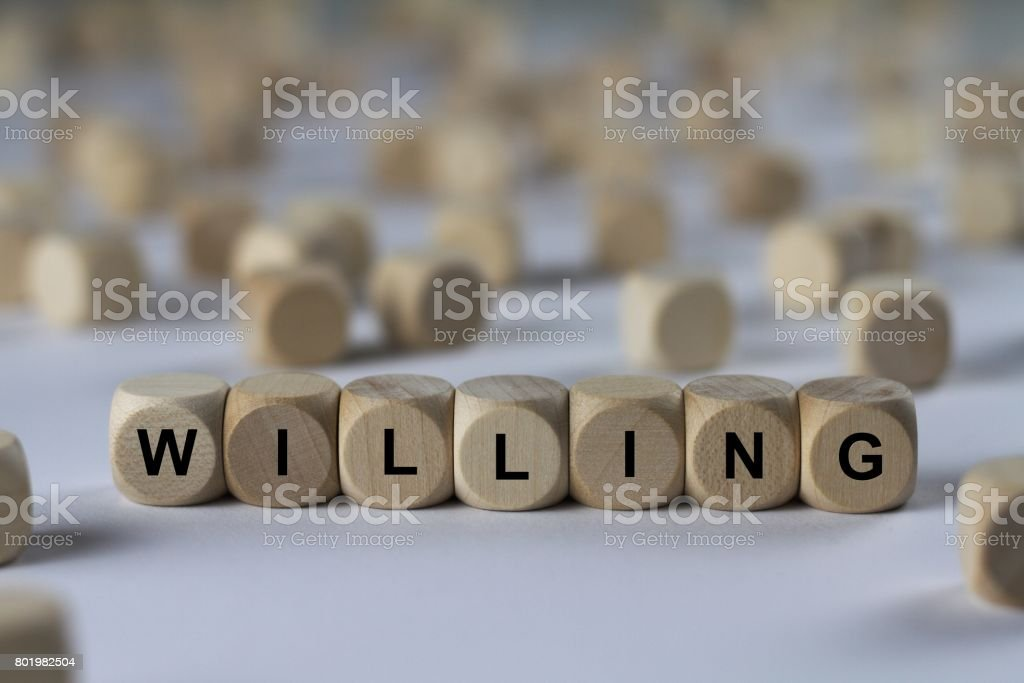 willing - cube with letters, sign with wooden cubes stock photo