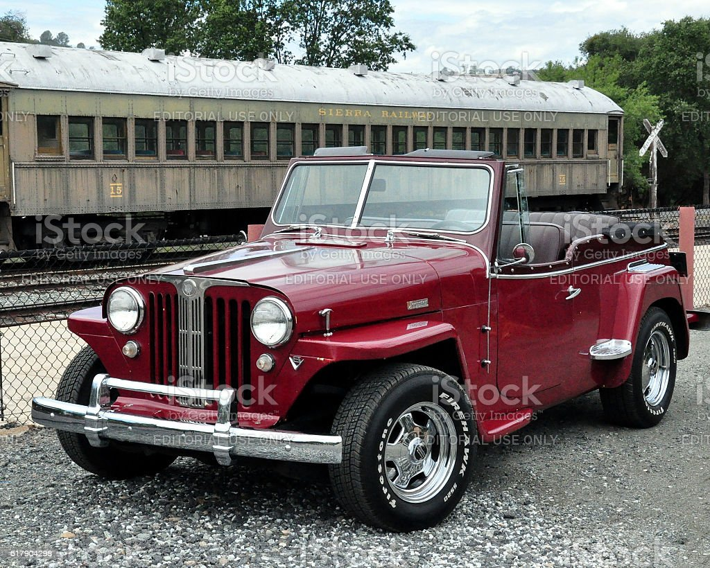 Willys Jeepster parked by a vintage rail car stock photo