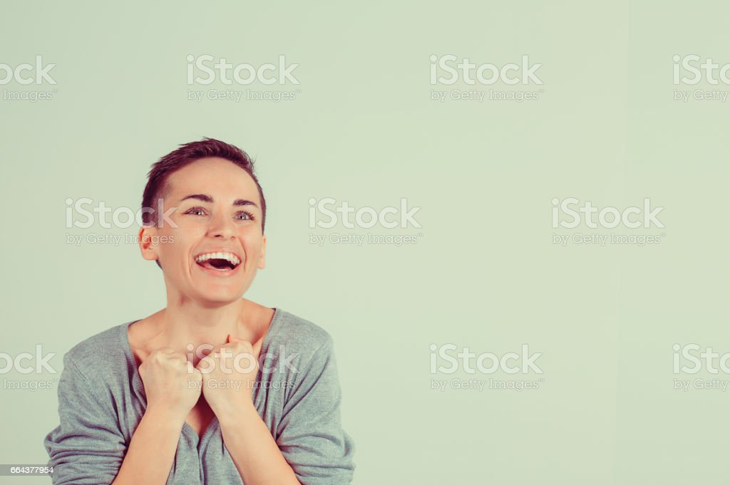 Win. Closeup portrait happy ecstatic winning successful young woman fist hand in the air celebrating being winner isolated green background. Positive human emotions body language. Achievement concept stock photo