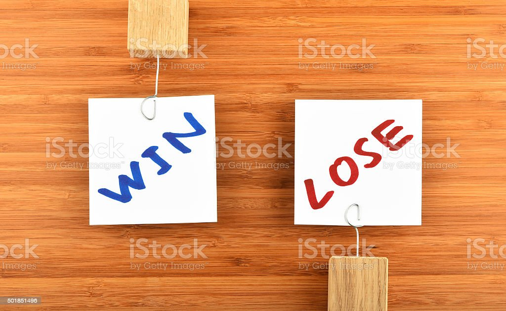 Win lose two paper notes in different directions on wood royalty-free stock photo