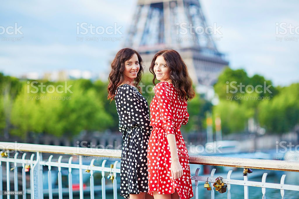 Еwin sisters in front of the Eiffel tower in Paris stock photo