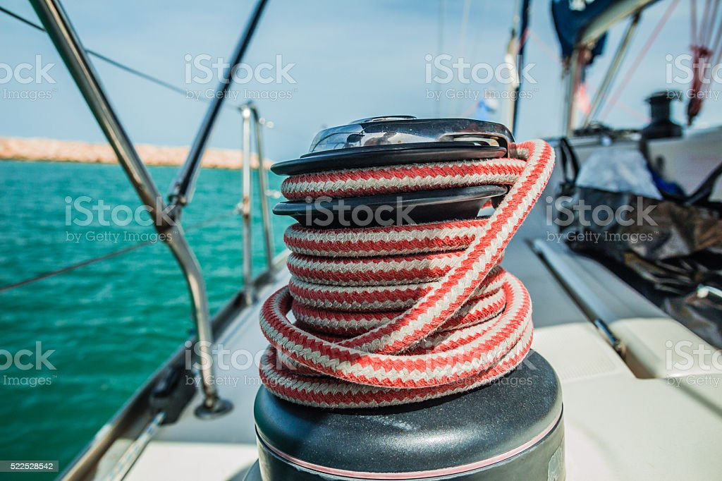 Winch with red and white rope on sailing boat stock photo