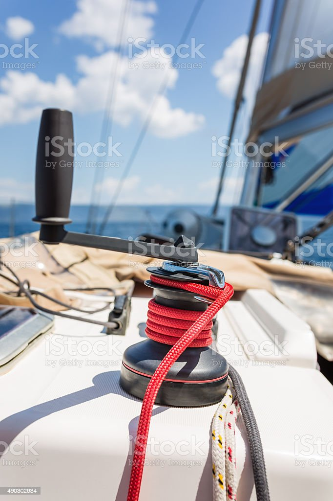 Winch with rope and handle on sailboat stock photo