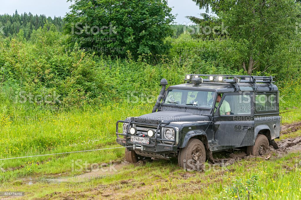 Winching of Land Rover Defender vehicle sunk in mud stock photo