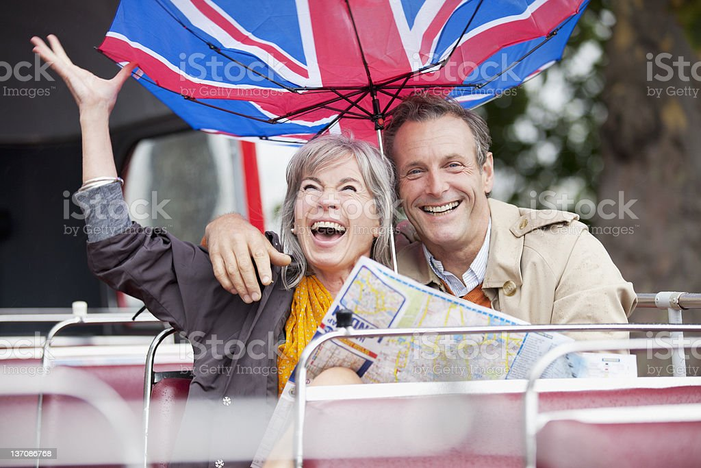 Wind flipping British flag umbrella over happy couple with map on double decker bus royalty-free stock photo