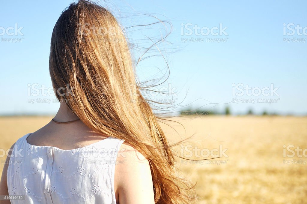 Wind flutters young girls hair stock photo