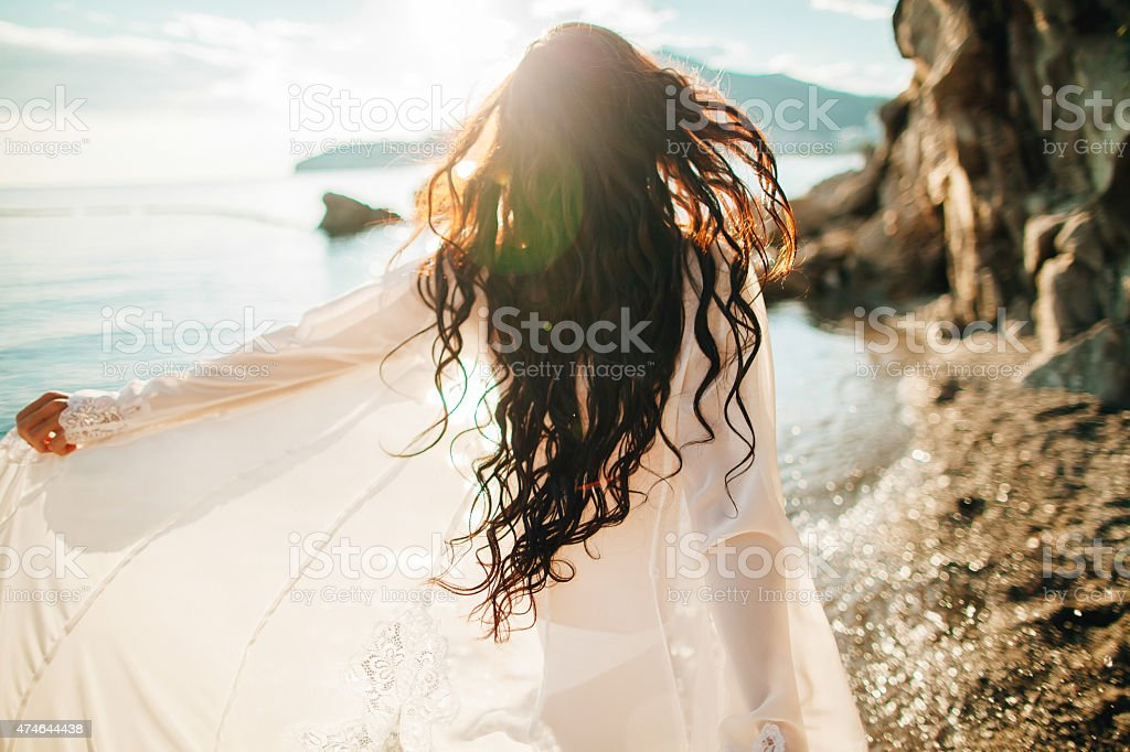 wind in hair dreamy girl with sunflare on beach stock photo