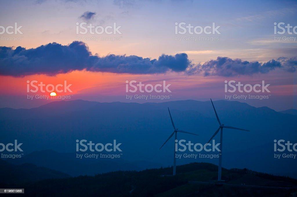 wind power generator on the mountain at moody sunrise stock photo