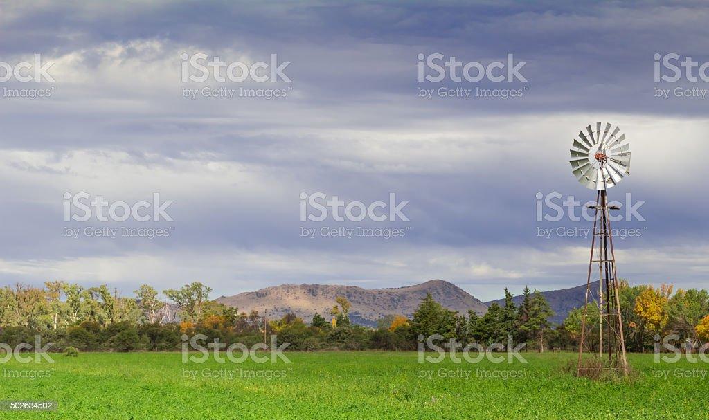 Wind pump in a field stock photo