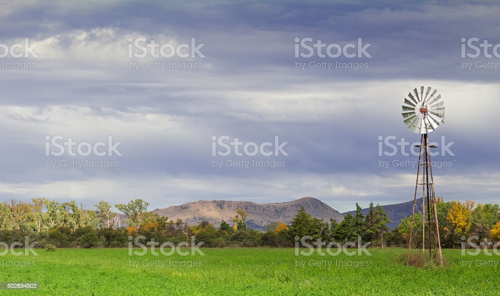 Wind pump in a field stock photo