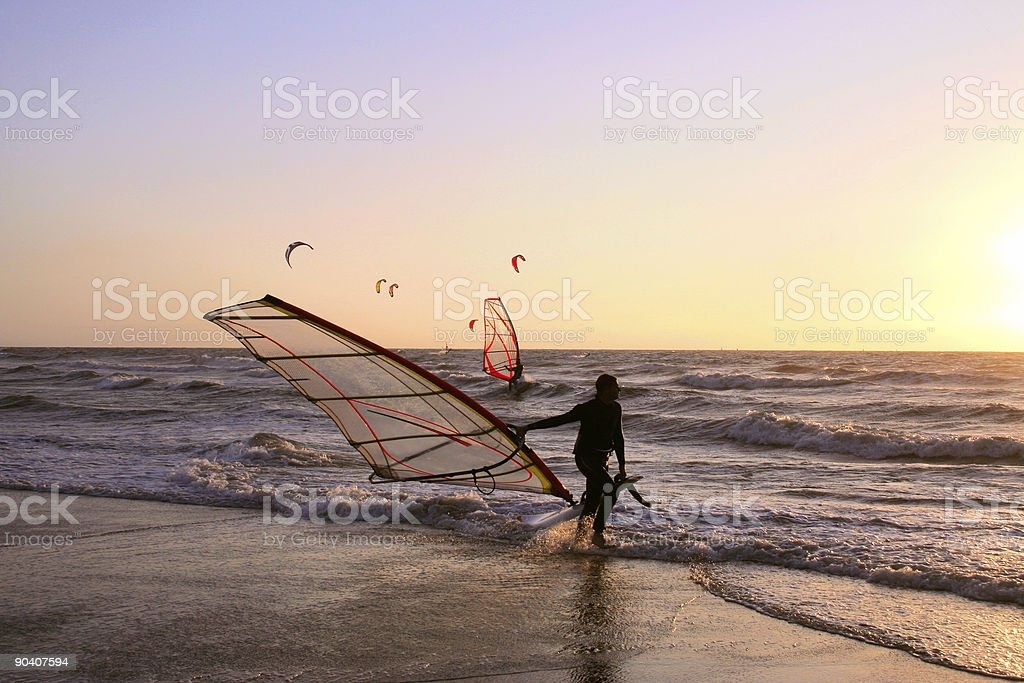 Wind surfer coming out of the surf at dusk royalty-free stock photo